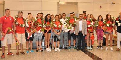 Altın madalyalı genç  yüzücüler, havalimanında çiçeklerle karşılandı